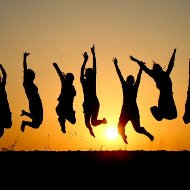 Friends joyfully jumping sunset